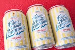 Ice cold canned cocktail Fishers Island Lemonade on red background with condensation.